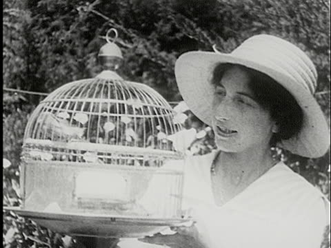 ms, b/w, woman wearing sun hat holding bird cage outdoors, usa - sun hat stock videos & royalty-free footage