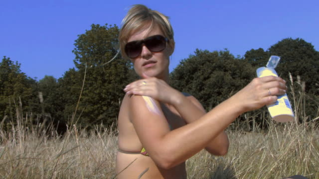 MS Woman wearing sunglasses applying sun cream in field / Hampstead, United Kingdom