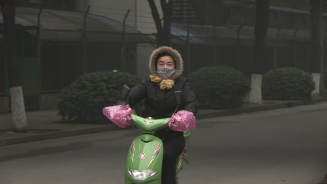 ms, ts, woman wearing surgical mask riding scooter, shanghai pudong international airport, shanghai, china - obsessive stock videos & royalty-free footage