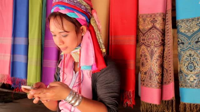 vrouw die dragen de traditionele met mobiele telefoon tegen een weven in dorp