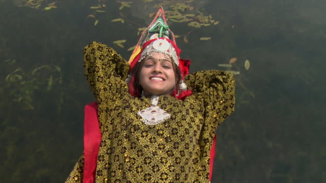 OH MS ZI CU Woman wearing traditional clothing floating in shikara on Dal Lake / Srinagar, Jammu and Kashmir, India
