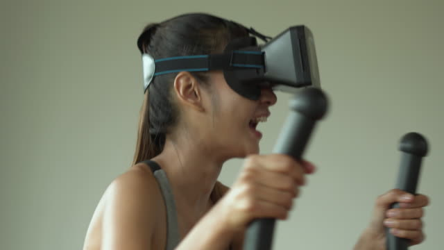 woman wearing virtual reality goggles using elliptical machine at home - relaxation exercise stock videos & royalty-free footage