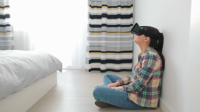 Woman wearing virtual reality headset at home.