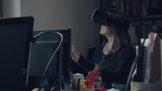 Woman wearing virtual reality headset at office