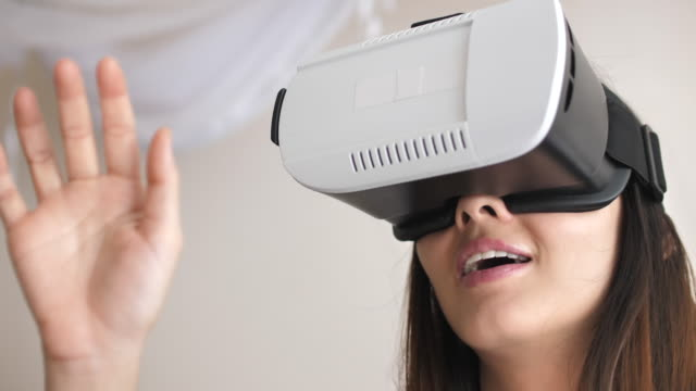 woman  wearing vr headset for playing a video game in virtual reality - eyesight stock videos & royalty-free footage