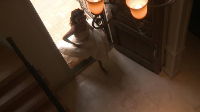 ws slo mo woman wearing wedding dress entering in house / jacksonville, florida, usa - entrata video stock e b–roll