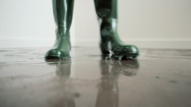 woman wearing wellington boots walking on flooded floor - inondazione video stock e b–roll