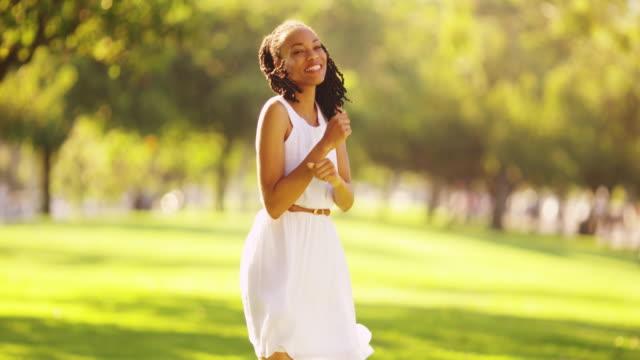 vidéos et rushes de woman wearing white dress standing in a field - robe blanche