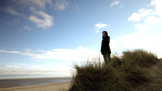 woman wearing winter coat stands in seagrass looking out to sea - winter coat stock videos & royalty-free footage