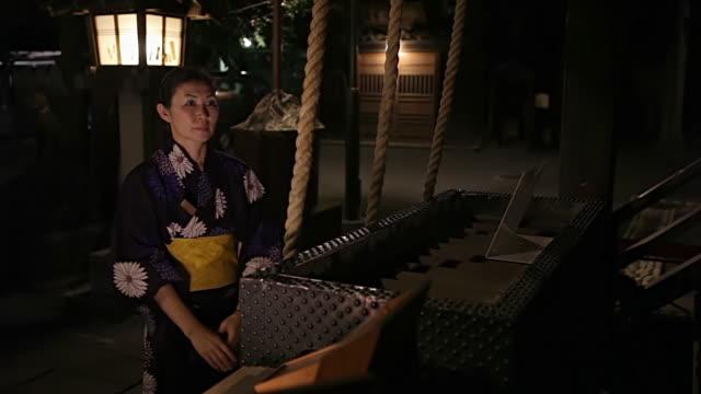 ms woman wearing yukata is praying at ontakesan shrine in / tokyo, japan - yukata video stock e b–roll
