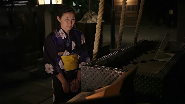 ms woman wearing yukata is praying at ontakesan shrine in / tokyo, japan - respect点の映像素材/bロール
