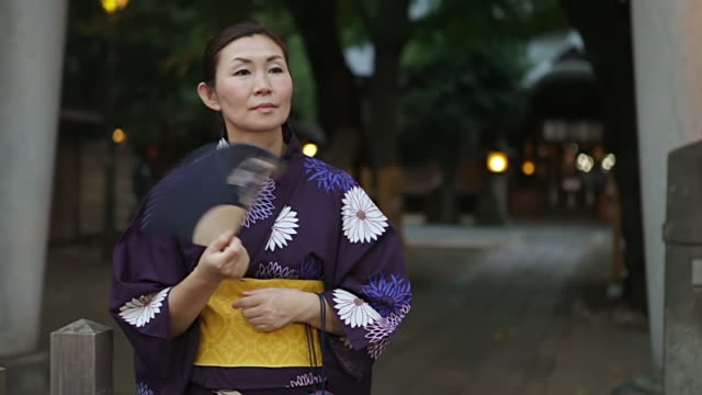 MS Woman wearing yukata (Japanese traditional costume) is waiting in front of a shrine in / Tokyo, Japan