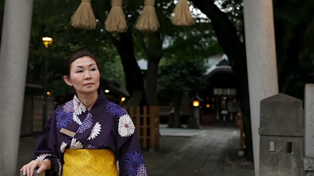 MS TD Woman wearing yukata (Japanese traditional costume) is waiting in front of a shrine in / Tokyo, Japan