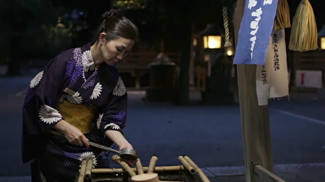 MS Woman wearing yukata is washing her hands at water fountain before she enters Ontakesan shrine in / Tokyo, Japan