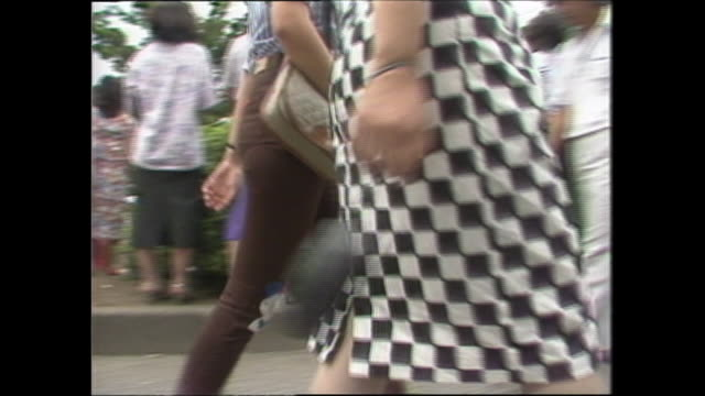 a woman wears a checkered skirt as she walks with a friend. - 1980~1989年点の映像素材/bロール