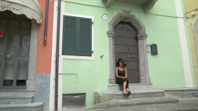a woman wears a hat while traveling to a luxury resort town near lake como, italy, europe. - slow motion - white doorway stock videos & royalty-free footage