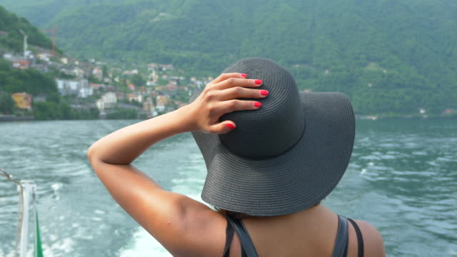 vídeos de stock e filmes b-roll de a woman wears a hat while traveling to a luxury resort town on a ferry near lake como, italy, europe. - slow motion - riqueza