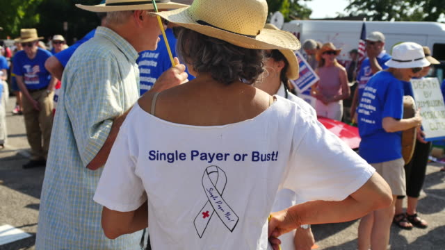 A woman wears a shirt in support of single payer health insurance before the Bloomington Indiana 4th of July parade in 2017 Many in the parade were...