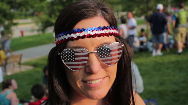 a woman wears american flag sunglasses as hundreds of grateful dead fans hang out on a lawn south of soldier field the grateful dead performed five... - one young woman only stock videos & royalty-free footage