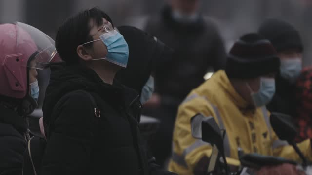 woman wears protective face masks as she waits for the stoplight on march 3 in beijing, china.in march, the 13th national people's congress will hold... - beijing stock videos & royalty-free footage