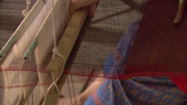 a woman weaves silk threads on a loom. - menschliche gliedmaßen stock-videos und b-roll-filmmaterial