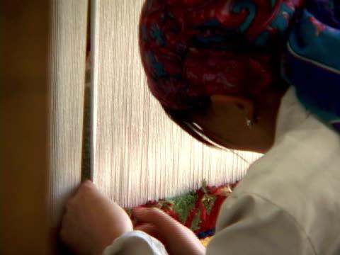 CU, ZO, MS, Woman weaving carpet in workshop, Lhasa, Tibet, China