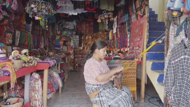 vidéos et rushes de woman weaving mayan traditional costume at a souvenir shop - maya