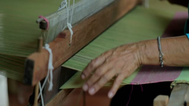 woman weaving silk in traditional way at manual loom in thailand, slow motion - civiltà maya video stock e b–roll