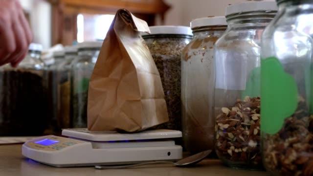 vidéos et rushes de la femme pèse ses graines qu'elle a achetées à l'atelier de santé durable - graine
