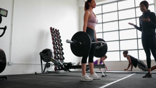 woman weightlifting with personal trainer - direction stock videos & royalty-free footage
