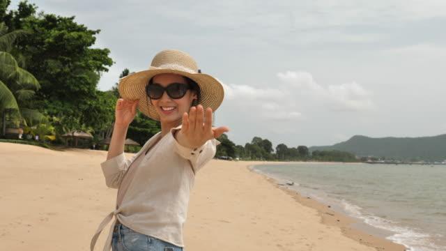 vídeos de stock e filmes b-roll de woman welcome you to walk with her on beach. female tourist is enjoying summer vacation travel showing welcoming gesture smiling happy - estilo de vida alternativo