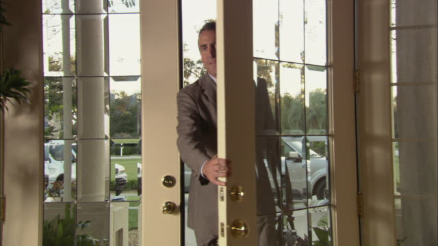 ms zo woman welcoming husband returning from work, handing him cocktail in entrance hall / jacksonville, florida, usa - aktentasche stock-videos und b-roll-filmmaterial