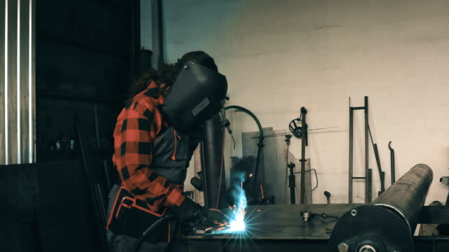 frau schweißer in workshop 4k - schweißen stock-videos und b-roll-filmmaterial