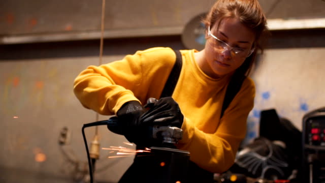 woman welder in workshop - persona di sesso femminile video stock e b–roll