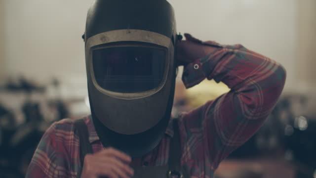 cu woman welder putting on her helmet in a repair shop - welding stock videos & royalty-free footage