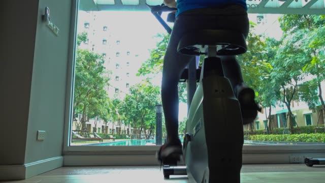 vidéos et rushes de femme tout en équitation vélo intérieur dans le studio de cyclisme. - vélo d'appartement