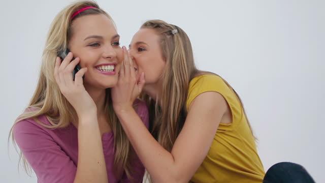 vídeos y material grabado en eventos de stock de woman whispering to her friends whos using a phone - cinta de cabeza