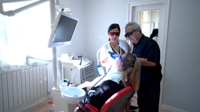 woman whitening teeth at the dentist - teeth whitening stock videos and b-roll footage