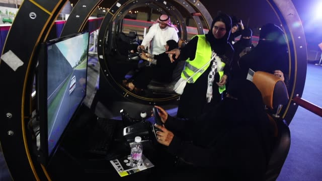 vídeos de stock, filmes e b-roll de a woman who is wearing a traditional muslim niqab tries out a car driving simulator during an outdoor educational driving event for women as other... - vestimenta religiosa