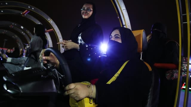 a woman who is wearing a traditional muslim niqab tries out a car driving simulator during an outdoor educational driving event for women as other... - censura video stock e b–roll