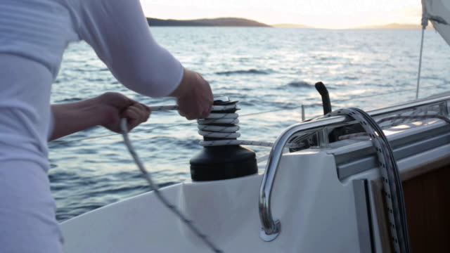cu woman winding rope around winch on yacht. - ブラック島点の映像素材/bロール