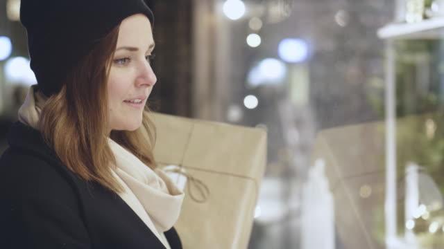 vídeos y material grabado en eventos de stock de mujer ventana comercial durante vacaciones de navidad - escaparate de tienda