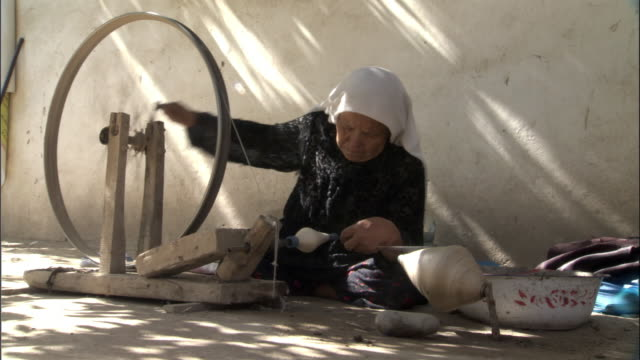 woman winds raw silk onto small bobbin, hetian, xinjiang province, china, - bbc stock videos and b-roll footage