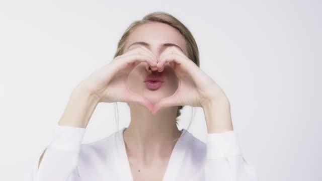 kvinna winking och puckering genom hjärta form - rynka ihop ansiktet bildbanksvideor och videomaterial från bakom kulisserna