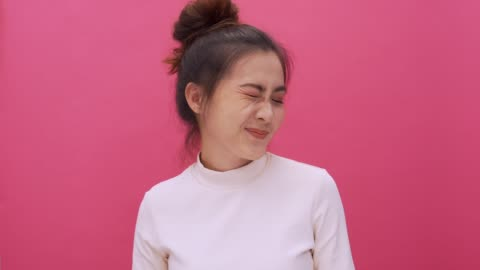 woman winks of one eye look at camera isolated pink background 4k - falling in love stock videos & royalty-free footage
