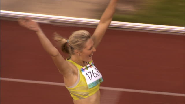 stockvideo's en b-roll-footage met ha ms pan woman winning track event and waving and blowing kisses to the crowd/ sheffield, england - atlete