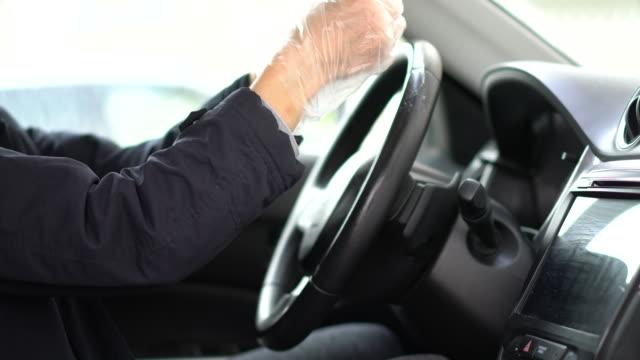 vídeos de stock e filmes b-roll de woman wipes car steering wheel with gloves and mask - sem higiene