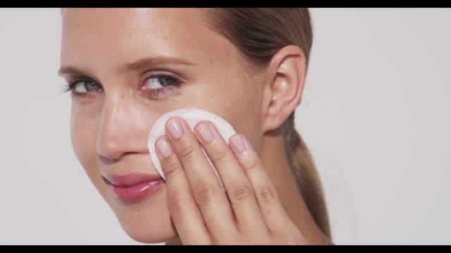 vídeos de stock, filmes e b-roll de woman wipes cotton pad over face - aplicando
