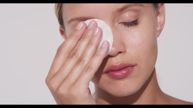 woman wipes cotton pad over right eye - pampering stock videos & royalty-free footage