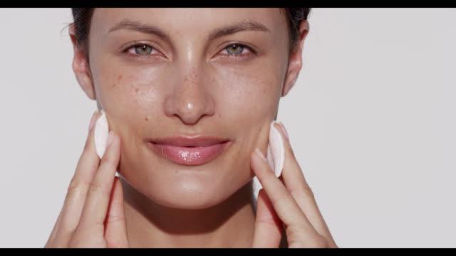 vidéos et rushes de woman wipes cotton pads over face with both hands - trentenaire